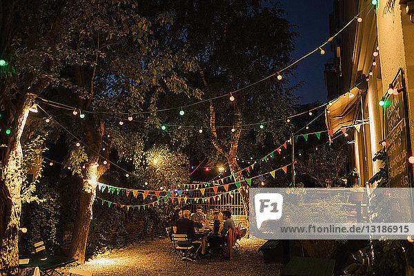 Multiethnische Freunde genießen Dinnerparty im beleuchteten Hinterhof