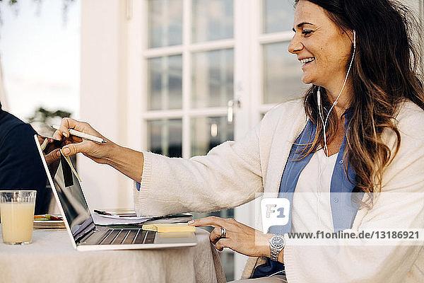 Lächelnde reife Frau trägt Kopfhörer  während sie in der Ferienvilla einen Laptop benutzt