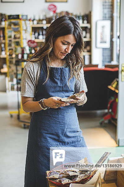 Weibliche Mitarbeiterin prüft Lebensmittel  während sie im Feinkostladen steht