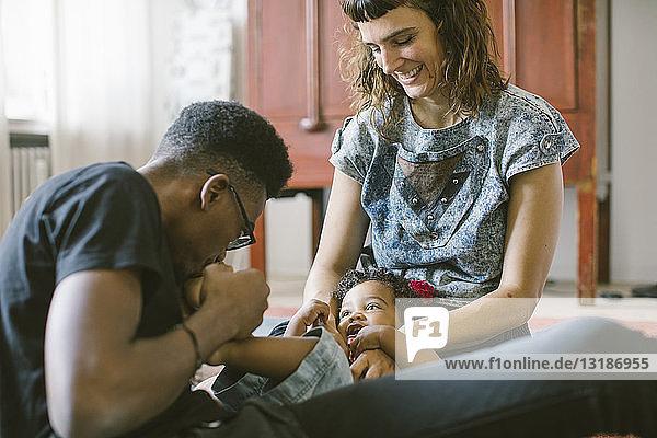 Vater küsst Fuß der Tochter  die zu Hause auf dem Schoß der Mutter liegt