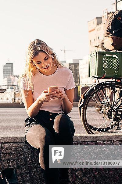 Lächelnde junge Frau benutzt Mobiltelefon  während sie auf einer Stützmauer an einer Straße in der Stadt sitzt