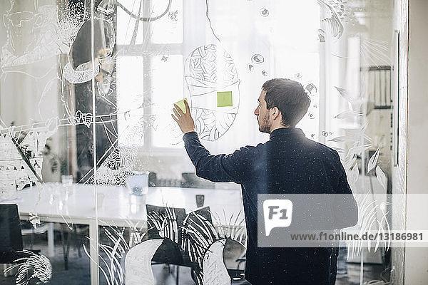 Rückansicht eines kreativen Geschäftsmannes  der im Büro eine Haftnotiz auf Glas klebt