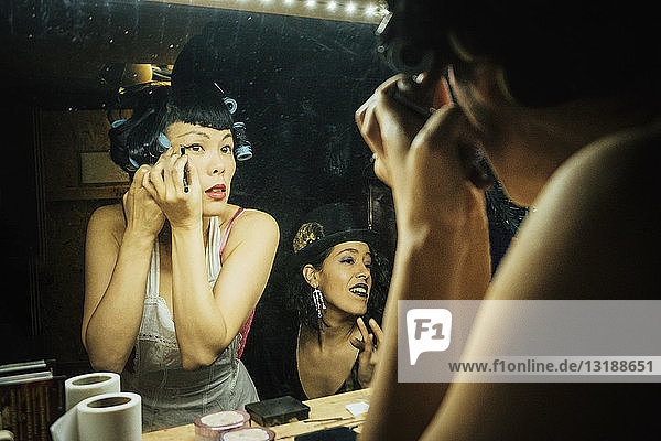 Female burlesque performers getting ready  applying makeup at dressing room mirror