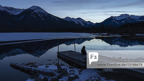 Woman sitting on tranquil winter lake dock with mountain view at night  Banff  Alberta  Canada Woman sitting on tranquil winter lake dock with mountain view at night, Banff, Alberta, Canada