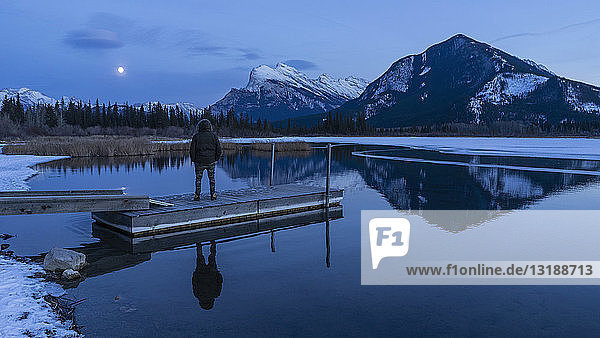 Woman on tranquil winter lake dock  looking at full moon above mountains  Banff  Alberta  Canada Woman on tranquil winter lake dock, looking at full moon above mountains, Banff, Alberta, Canada