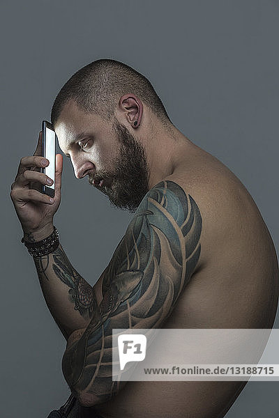 Portrait serious bare chested man with tattoos holding smart phone