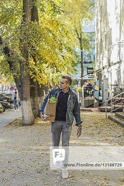 Man carrying groceries on autumn sidewalk