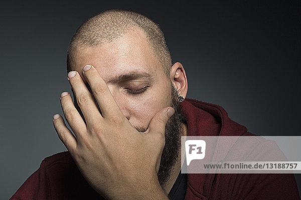 Mann mit geschlossenen Augen  der sein Gesicht mit den Händen bedeckt