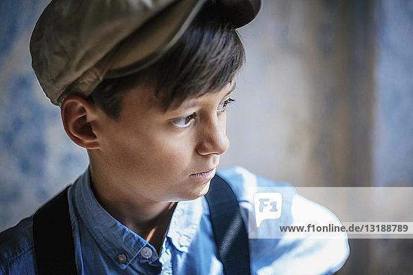 Thoughtful boy in cap looking away