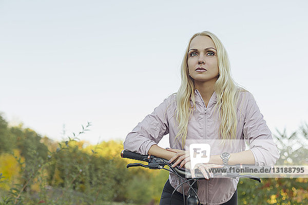 Confident  serious woman riding bicycle in park