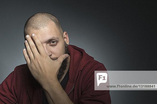 Porträt Mann bedeckt Gesicht mit Hand