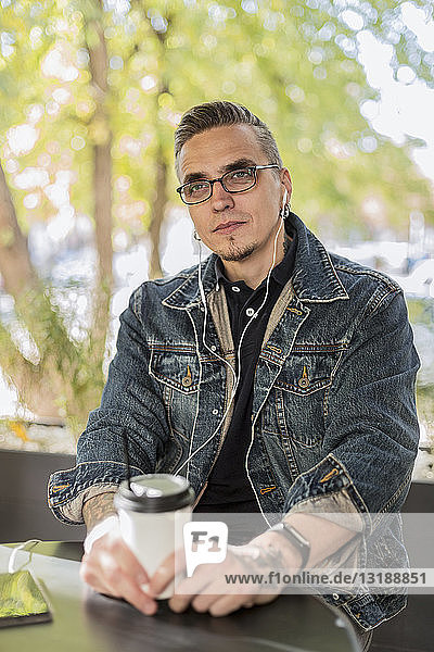 Man listening to music with earbuds  drinking coffee in cafe
