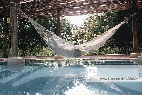 Woman in hammock over swimming pool