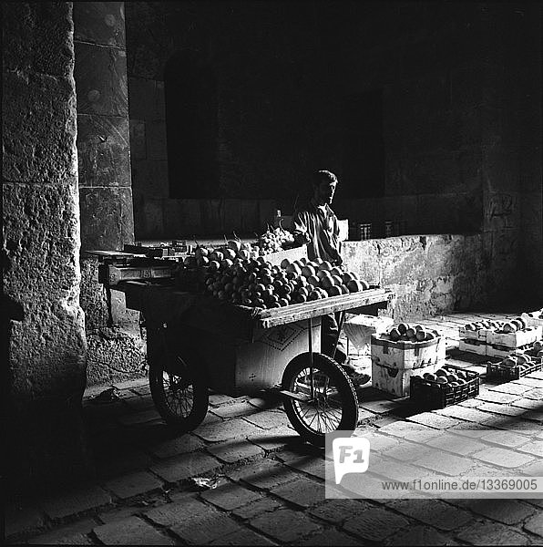 Fruit stall vendor in shadow