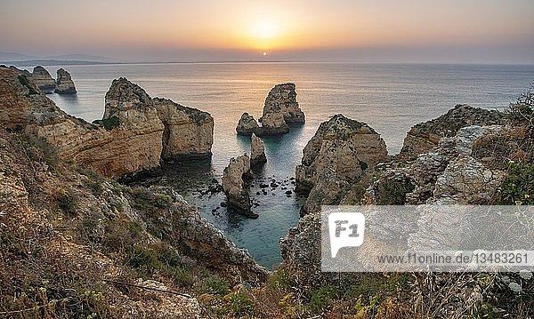 Sonnenaufgang über dem Meer  schroffe Felsenküste aus Sandstein  Felsformationen im Meer  Ponta da Piedade  Algarve  Lagos  Portugal  Europa