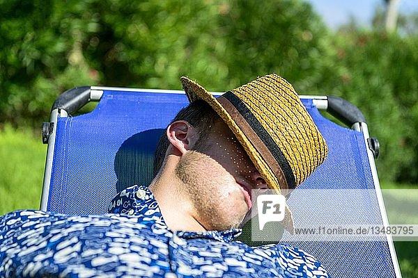 Junger Mann mit Strohhut schläft auf Sonnenliege im Urlaub  Italien  Europa