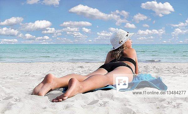 Mädchen mit Sonnenhut am weißem Sandstrand mit türkisem Meer liegend auf einem blauen Badetuch
