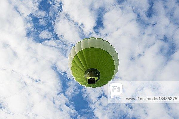 Grüner Grüner Heißluftballon vor blauem Himmel mit Wolken  Frankreich  Europa
