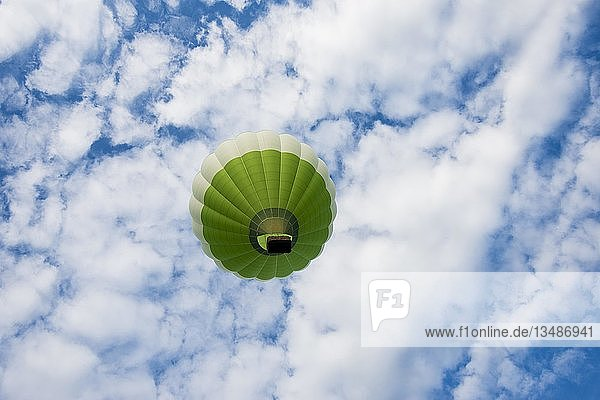 Grüner Heißluftballon vor blauem Himmel mit Wolken  Frankreich  Europa