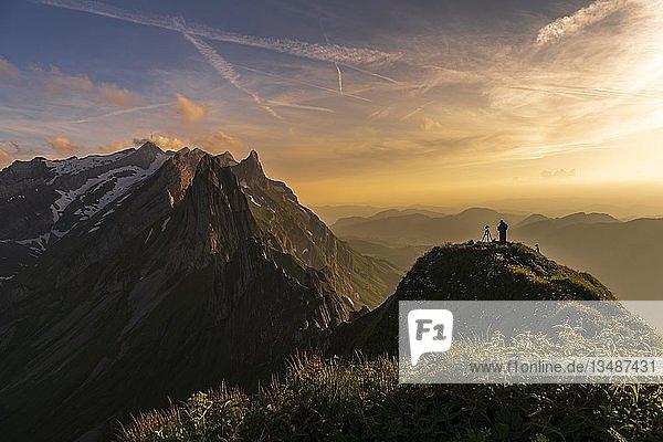 Fotograf auf grasigem Grat bei Sonnenuntergang mit Säntisgipfel im Hintergrund  Wasserauen  Appenzell  Schweiz  Europa