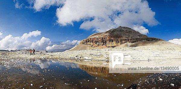 Wanderer auf dem Sellamassiv mit Spiegelung des Piz Boe Gipfels in einem Schmelzwassersee  Sellajoch  Südtirol  Italien  Europa