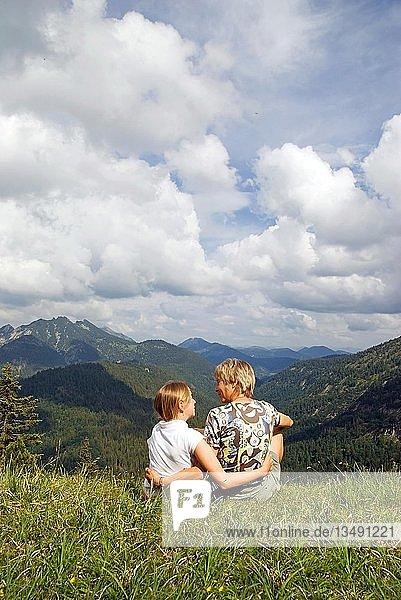 Mutter mit Kind sitzend auf einer Bergwiese bei Wildbad Kreuth  Bayern  Deutschland  Europa