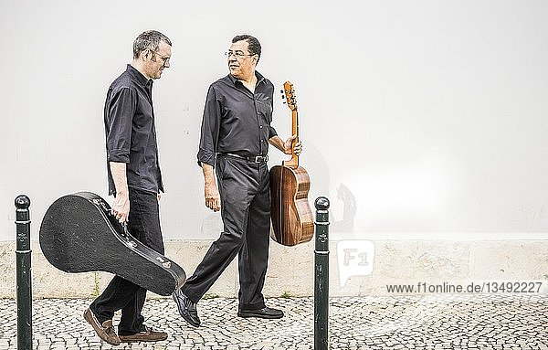 Two guitarists walking with their instruments on the pavement by the white wall  Alfama  Lisbon  Portugal  Europe