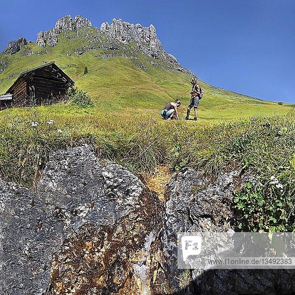 Kleine Quelle am Peitlerkofel mit Wanderer und Berghütte  Würzjoch  Villnöss  Dolomiten  Südtirol  Italien  Europa