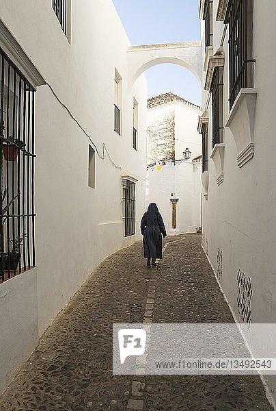 Nonne in einer Gasse mit weiß getünchten Häusern  weiße Stadt von Arcos de la Frontera  Cadiz-Provinz  Andalusien  Spanien  Europa