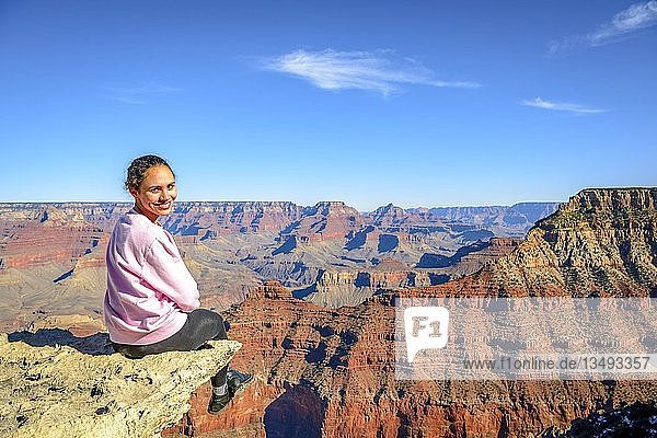 Junge lächelnde Frau  sitzt am Abgrund der gigantischen Schlucht des Grand Canyon  Blick vom Rim Trail  zwischen Mather Point und Yavapai Point  erodierte Felslandschaft  South Rim  Grand Canyon Nationalpark  bei Tusayan  Arizona  USA  Nordamerika