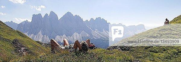 Bergwanderer entspannen im Aferer Geisler-Gebirge und genießen den Blick zur Geisler Gruppe  Villnösstal  Südtirol  Italien  Europa
