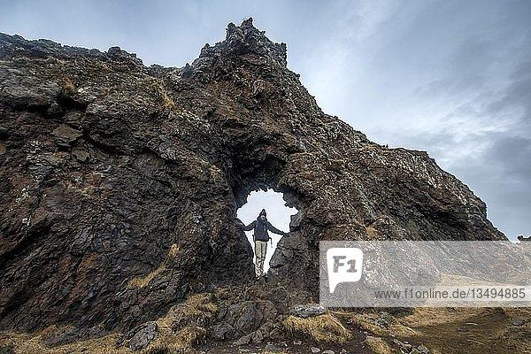 Junger Mann steht in Felsbogen  Vulkanfelsen am Strand von Djúpalónssandur  Halbinsel Snæfellsnes  Westisland  Island  Europa