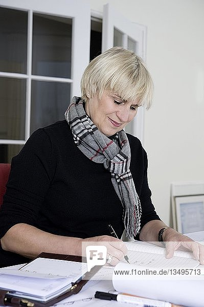 An architect sitting at her desk in her office and writing