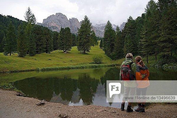 Mutter und Kind an einem kleinen See auf der Seceda Hochebene mit Sicht auf die Geisler Gruppe  Nationalpark Puez-Geisler  Wolkenstein  Südtirol  Italien  Europa