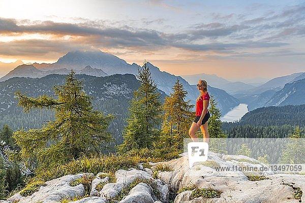 Wanderin blickt auf Bergpanorama  Ausblick über den Königssee von dem Feldkogel  links Watzmann Südspitze und Watzmann-Kinder  rechts Funtenseetauern  Sonnenuntergang  Nationalpark Berchtesgaden  Berchtesgadener Land  Oberbayern  Bayern  Deutschland  Europa