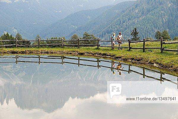 Frau mit Tochter am Wunlegersee bei Tiers mit dem Rosengartengebirge  das sich im See spiegelt  Südirol  Italien  Europa