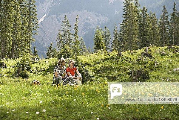 Frau und Kind sitzen in einer Wiese  Kleiner Ahornboden  Karwendel  Tirol  Österreich  Europa