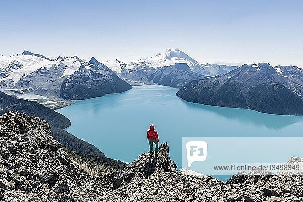 Ausblick vom Wanderweg Panorama Ridge  Wanderin auf einem Felsen  Garibaldi Lake  Guard Mountain und Deception Peak  hinten Gletscher  Garibaldi Provincial Park  British Columbia  Kanada  Nordamerika