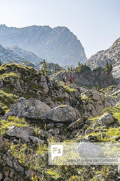 Zwei Wanderer auf einem Felsen  Berglandschaft  Stuhlgraben  Hinten Grießkogel  Steinernes Meer  Funtenseetauern  Nationalpark Berchtesgaden  Berchtesgadener Land  Oberbayern  Bayern  Deutschland  Europa