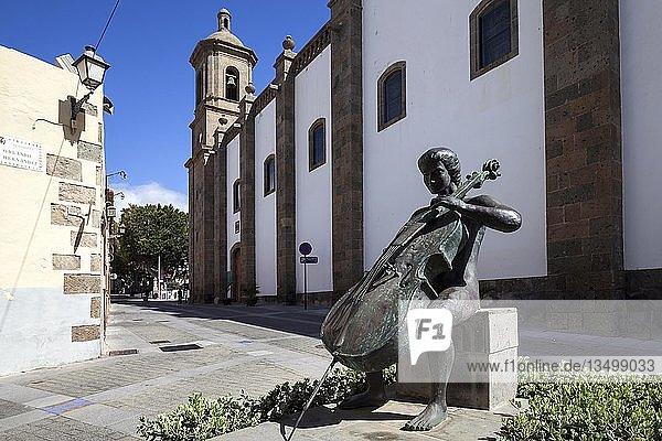 Bronze statue  cello player  Plaza Orlando Hernández  behind church Iglesia de San Sebastian  Agüimes  Gran Canaria  Canary Islands  Spain  Europe