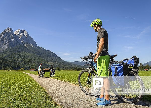 Cyclist on bike tour stands on bike path next to his mountain bike  in the back Zugspitze  Tegernauweg  near Grainau  crossing the Alps  Garmisch-Partenkirchen  Upper Bavaria  Bavaria  Germany  Europe