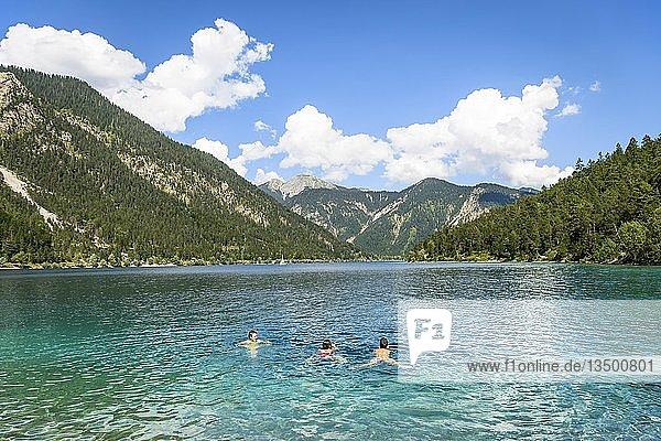 Drei Personen baden  schwimmen im Plansee  Ausblick vom Ufer  türkisfarbenes Wasser  Bergsee  Berglandschaft  Tiroler Alpen  Reutte  Tirol  Österreich  Europa