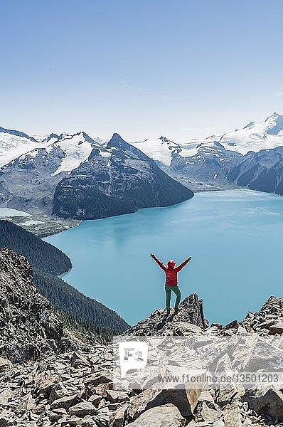 Ausblick vom Wanderweg Panorama Ridge  Wanderin auf einem Felsen streckt Arme in die Luft  Garibaldi Lake  Guard Mountain und Deception Peak  hinten Gletscher  Garibaldi Provincial Park  British Columbia  Kanada  Nordamerika