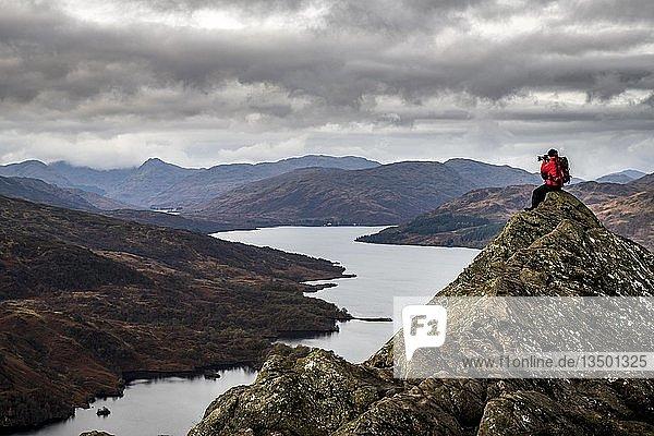 Gipfel des Ben Aán mit Fotograf  im Hintergrund Loch Katrine und die Highlands  Trossachs Nationalpark  Glasgow  Schottland  Großbritannien  Europa