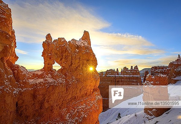 Sonnenstern scheint durch Loch in bizarrer Felsformation im Morgenlicht  verschneite Felslandschaft mit Hoodoos im Winter  Navajo Loop Trail  Bryce Canyon Nationalpark  Utah  USA  Nordamerika