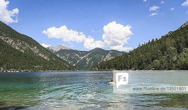Junger Mann badet  schwimmt im Plansee  türkisfarbenes Wasser  Bergsee  Berglandschaft  Tiroler Alpen  Reutte  Tirol  Österreich  Europa