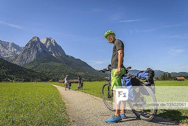 Fahrradfahrer auf Radtour steht auf Radweg neben seinem Mountainbike  hinter Zugspitze  Tegernauweg  bei Grainau  Alpenüberquerung  Garmisch-Partenkirchen  Oberbayern  Bayern  Deutschland  Europa