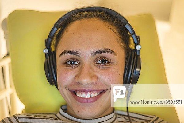 Junge Frau mit Kopfhörern lächelt  Berlin  Deutschland  Europa