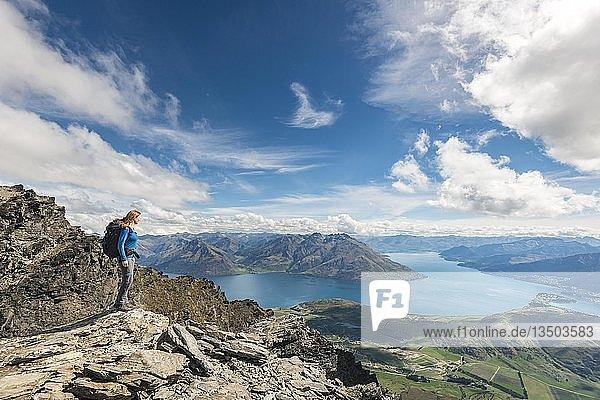 Wanderin steht auf Felsen der Bergkette The Remarkables  Blick auf Lake Wakatipu  Berge und Queenstown  Queenstown  Otago  Südinsel  Neuseeland  Ozeanien
