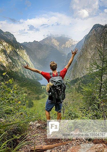 Junger Mann streckt Arme in die Luft  Wandern  Bergsteigen  Ausblick vom Rothsteig auf den Obersee  Königsee  Alpen  Berglandschaft  Nationalpark Berchtesgaden  Berchtesgadener Land  Oberbayern  Bayern  Deutschland  Europa